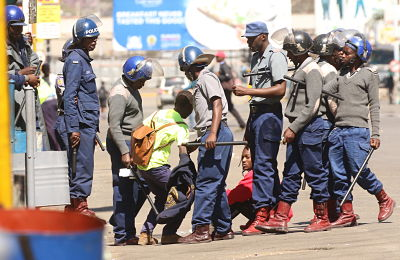 Police officers arrest protesters in Harare. Pic: Shaun Jusa/Xinhua/PA Images