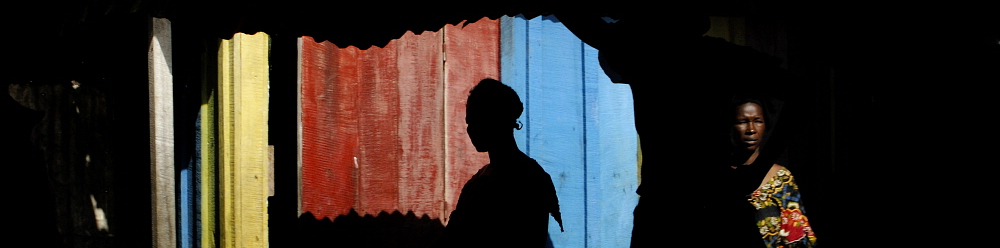 REPUBLIC OF CONGO Impfondo: A woman walks past a colourfully painted wooden building. Graeme Williams / Panos