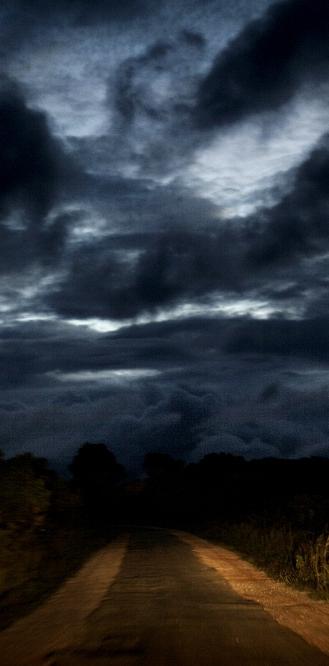 ZIMBABWE: Heavy cloud looms above a road. Robin Hammond / Panos
