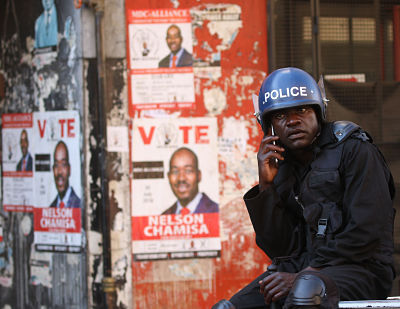 An anti-riot policeman talks on his cellphone near the MDC headquarters in Harare on Thursday 2 August. Pic: Xinhua/Shaun Jusa
