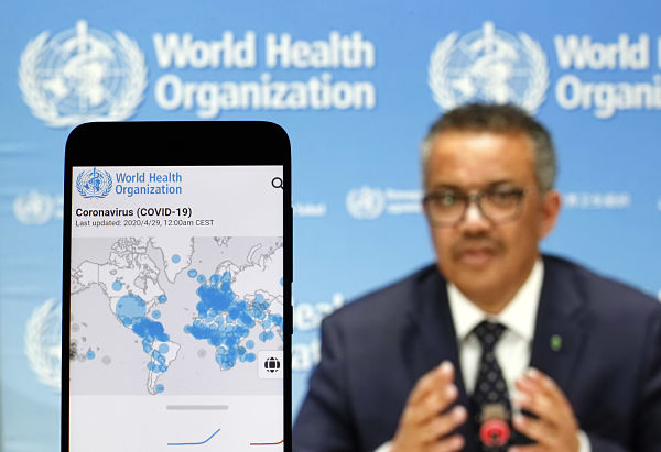 Tedros Adhanom Ghebreyesus seen on a screen with a WHO Covid-19 cases map displayed. Pic: Pavlo Gonchar/SOPA Images/SIPA USA/PA Images