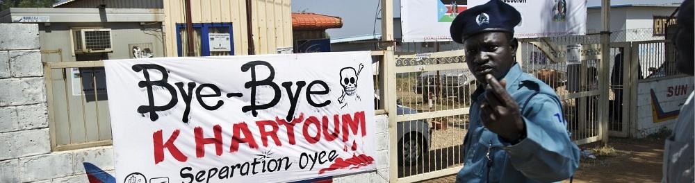 A policeman walks past a banner reading 'Bye-bye Khartoum' in Juba. Sven Torfinn / Panos