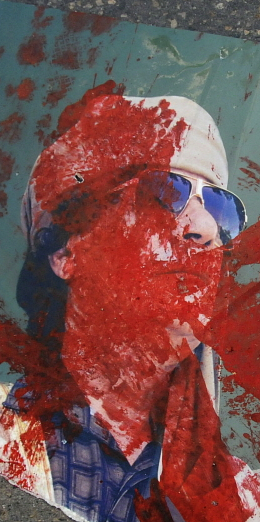 A picture of Colonel Gaddafi defaced with red paint lies on a street. Teun Voeten / Panos