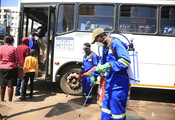 Staff members sanitise at a bus station in Harare, 1 April 2020. Pic: Shaun Jusa/Xinhua News Agency/PA Images