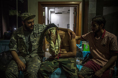 A wounded GNA fighter cries after some of his comrades were killed at Salah Al-Din front in July. Pic: Amru Salahuddien/Xinhua News Agency/PA Images