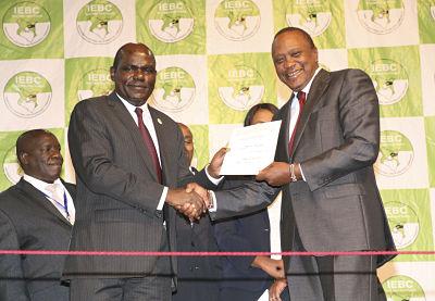 Uhuru Kenyatta receives his certificate as winner of the re-run presidential election from IEBC chairman Wafula Chabukati. Charles Onyango/Xinhua News Agency/PA Images