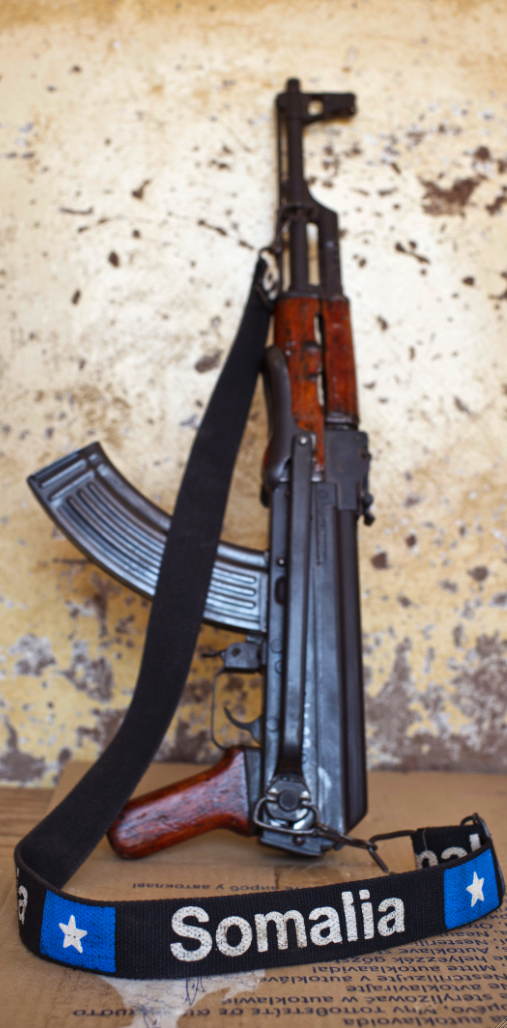 Gaalkaayo, Puntland. An AK47 rifle with a strap embroidered with 'Somalia' leans against a wall. Sven Torfinn / Panos