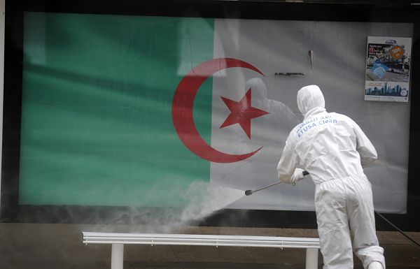 An Algerian health worker disinfects a bus stop in Algiers, 20 March 2020. Pic: Billal Bensalem/NurPhoto/PA Images