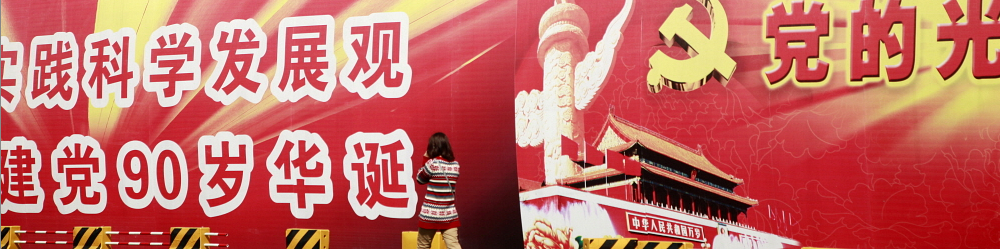 A woman walks past a hording displaying propaganda for the Chinese Communist Party. Qilai Shen / Panos