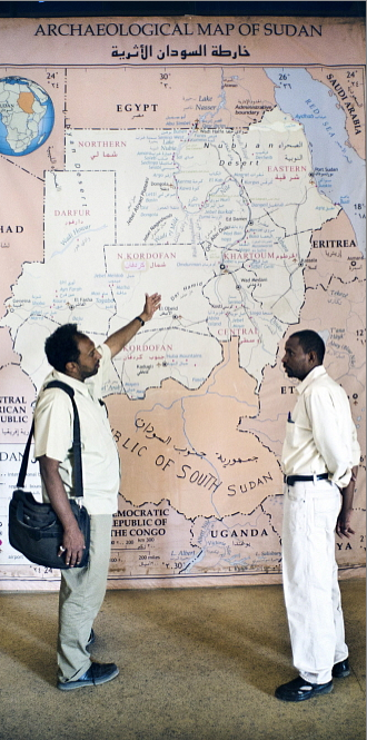 Two men discuss the new shape of their country in front of a map displayed in the lobby of the National Museum in Khartoum. Sven Torfinn / Panos