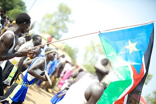 """""""South Sudan flag at independence"""" by sidelife is licensed with CC BY-ND 2.0. To view a copy of this license, visit https://creativecommons.org/licenses/by-nd/2.0/"""