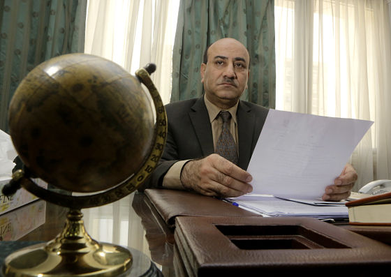 April 16, 2014 photo, Hesham Genena, the head of Egypt's oversight body, holds documents at his office in Cairo, Egypt. Genena has created uproar simply because he decided to actually do his job. The head of one of Egypt's foremost government oversight agencies, he says he has uncovered billions of dollars-worth of corruption, including in the country's most untouchable institutions, including the police, intelligence agencies, and the judiciary.(AP Photo/Amr Nabil)